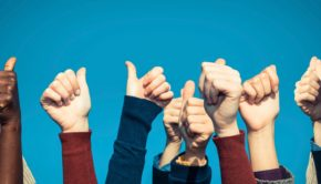 Hands doing thumbs-up gesture against blue background